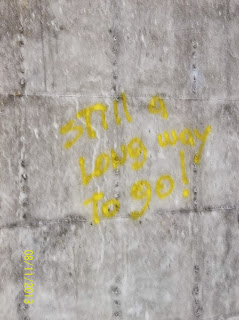 "Graffiti in Yellow on a Grey wall that says, ""Still a long way to go!"""