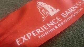 A broad red silky ribbon with the Barnsley Town Hall logo and the words Experience Barnsley Museum and Discovery Centre
