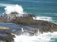 Foto de pescadores pescando em pedras arrecifes