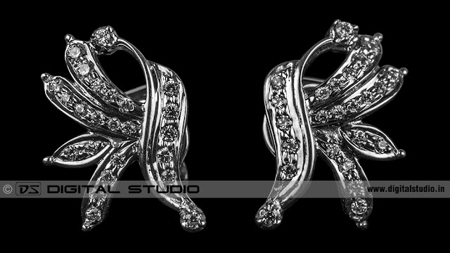 Real diamond earrings on black background