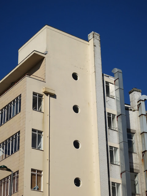 Concrete building with porthole windows against deep blue sky.