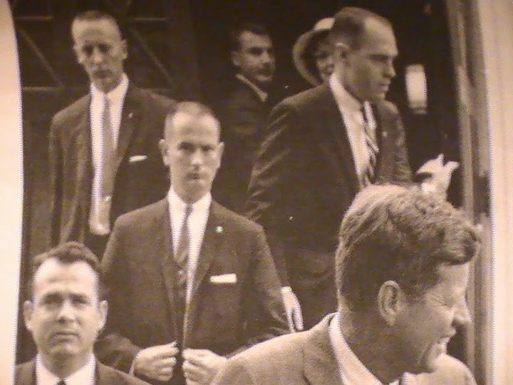 Agent Ken Wiesman (bottom left), Ned Hall II (buttoning suit), Ernie Olsson (top, left) etc.