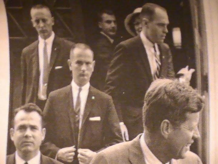 Agent Ken Wiesman (bottom left), Ned Hall II (buttoning suit), Ernie Olsson (top, left) etc.