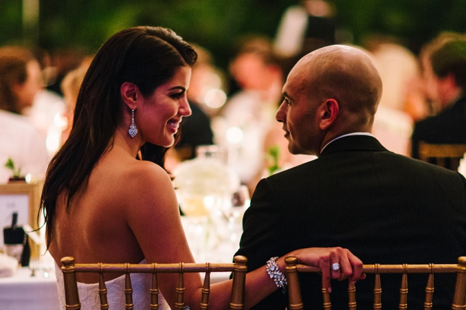 the bride and groom share a tender moment during dinner