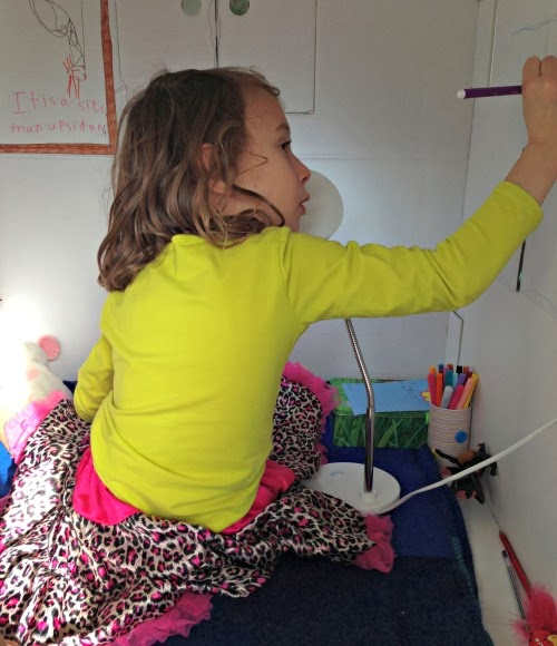 Child drawing on the walls inside a cardboard play house