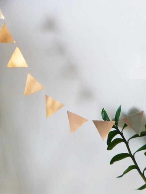DIY Wimpelkette in Kupfer vor grüner Pflanze
