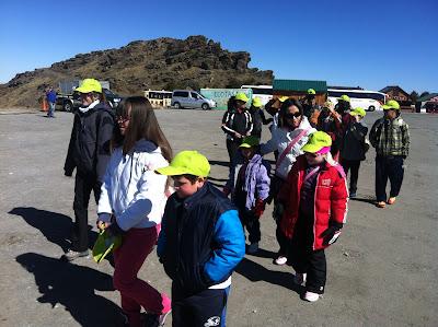 La imagen muestra a todos los alumnos y profesores con las gorras de la ONCE y andando hacia la zona de trineos.
