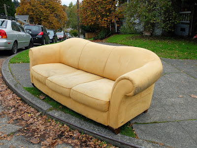 yellow couch sits curbside.