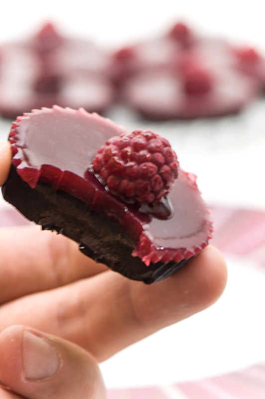 Raspberry and chocolate tarts bite in hand