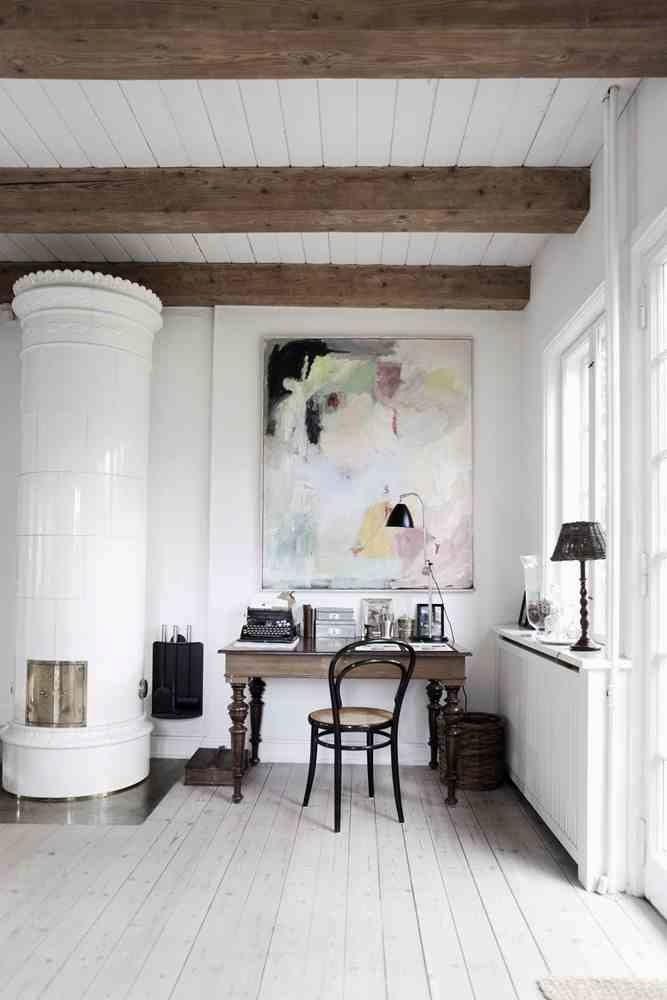 Biała drewniana podłoga, skandynawski biały piec, drewniane biurko i czarne dodatki