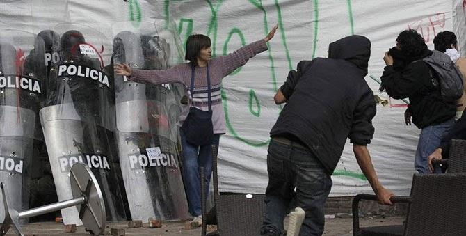 Женщина защищает спрятавшихся за щитами полицейских от разъяренных демонстрантов в Боготе, Колумбия, 2013 год.