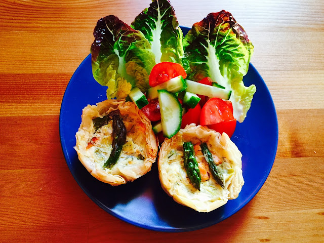 Two smoked salmon and asparagus tartlets on a plate