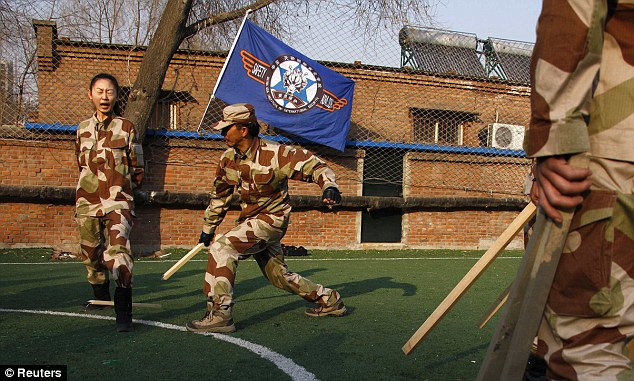 Beating: An instructor from Tianjiao Special Guard Consultant Ltd smashes a piece of wood over a recruit's leg