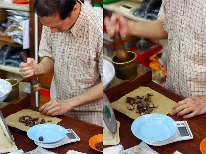 pounding nutmeg for traditional chinese medicine and for burning as incense for a prayer offering
