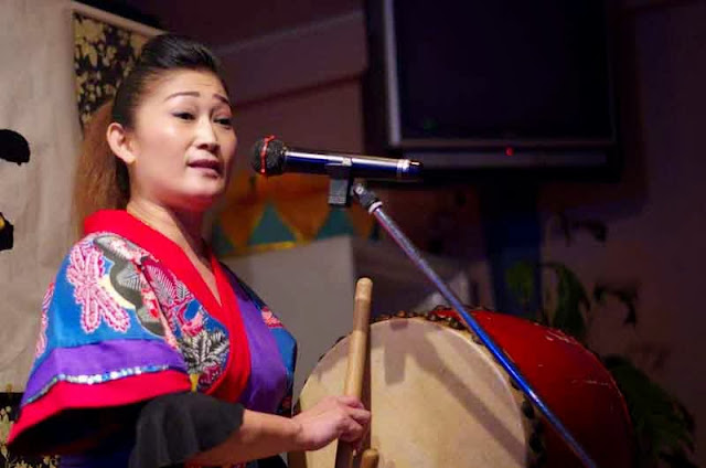 woman sings and plays drum in  okinawa