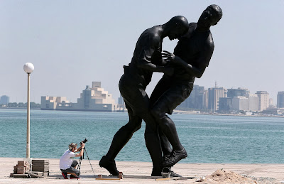 A photographer takes pictures of a bronze sculpture by French Algerian born artist Adel Abdessemed during its installation on October 4, 2013 on the Corniche in Doha after it was bought by the Qatar Museums Authority. The statue, titled Coup de Tete immortalizes the headbutt given by the French former football champion Zinedine Zidane to Italian player Marco Materazzi during the World Cup final in 2006.