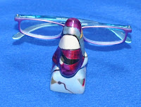 purple/blue reader glasses on a nose eyeglass holder