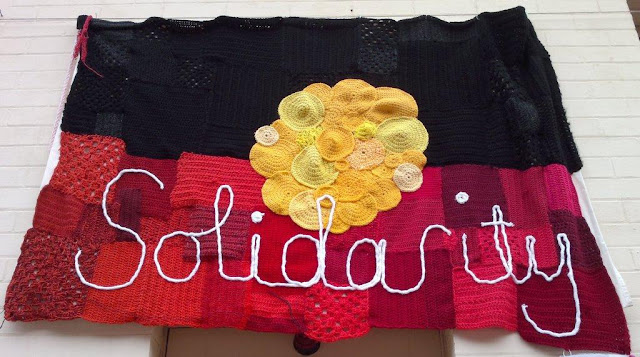 A large patchwork Australian Aboriginal flag in black, yellow and red with the word 'Solidarity' in white across the red strip.