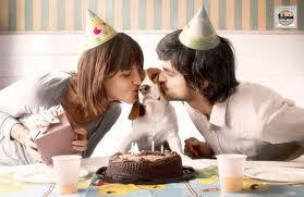 woman and man kissing a dog in front of a birthday cake.
