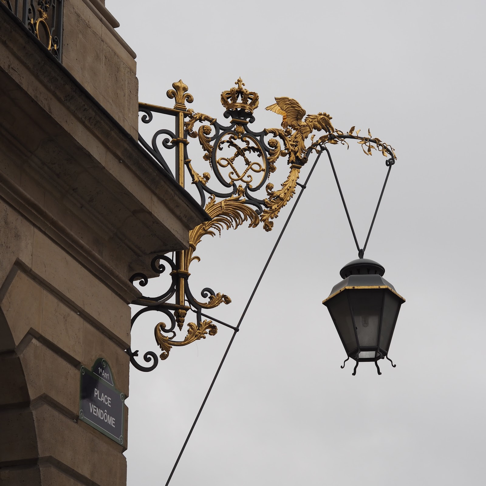 gold lamp on side of building, paris