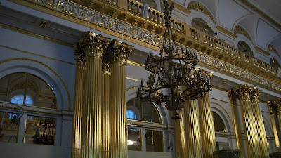 A chandelier in front of golden pillars inside the Hermitage.