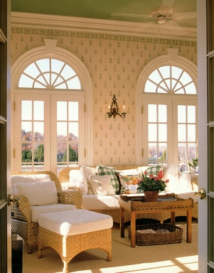 [A light living room with wicker armchairs and rounded windows]