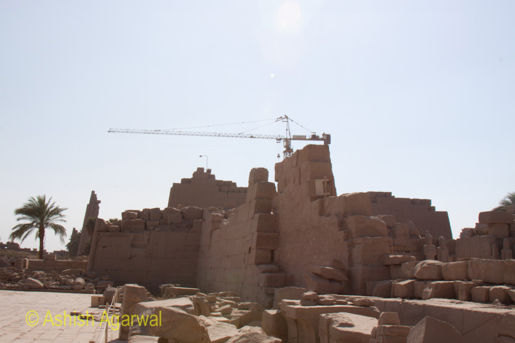 Collapsed structures against the backdrop of a crane at the Karnak temple in Luxor