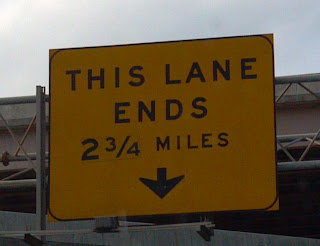 sign that says this lane ends in two and three quarter miles