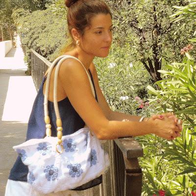 Chica apoyada en una barandilla con un bolso de granny square flor africana