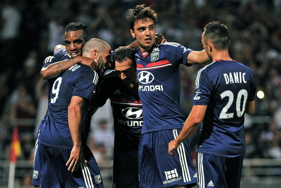 Clément Grenier celebrates with Lyon teammates after scoring a goal against Real Madrid