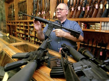 man holding up gun in gunshop in America