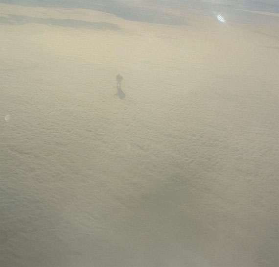 Mysterious Shadow Figure Walking on top of clouds Captured By Plane Passenger