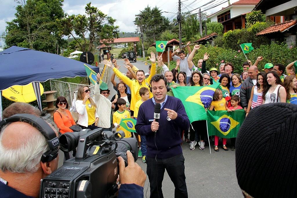 Com torcida ao fundo, Erick Faria, da Rede Globo, anuncia ao vivo a chegada da Seleção a Teresópolis