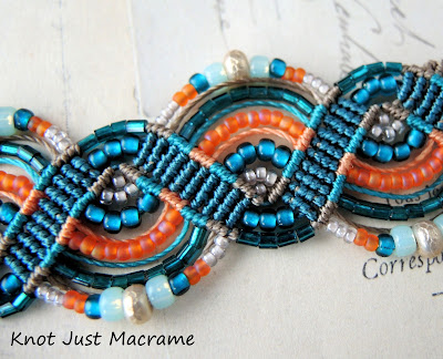 Close up of beaded macrame bracelet in teals and orange
