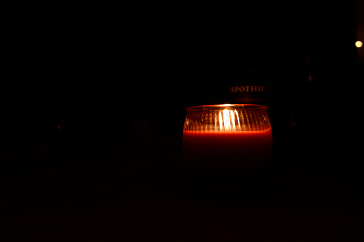 lone red candle in the darkness