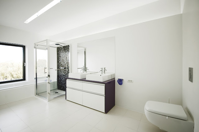 Modern white bathroom in the Black On White House by Parasite Studio