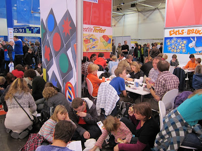 A photo at Spiel 2011 taken in Hall 11 showing the people sitting at tables and in the aisles playing games