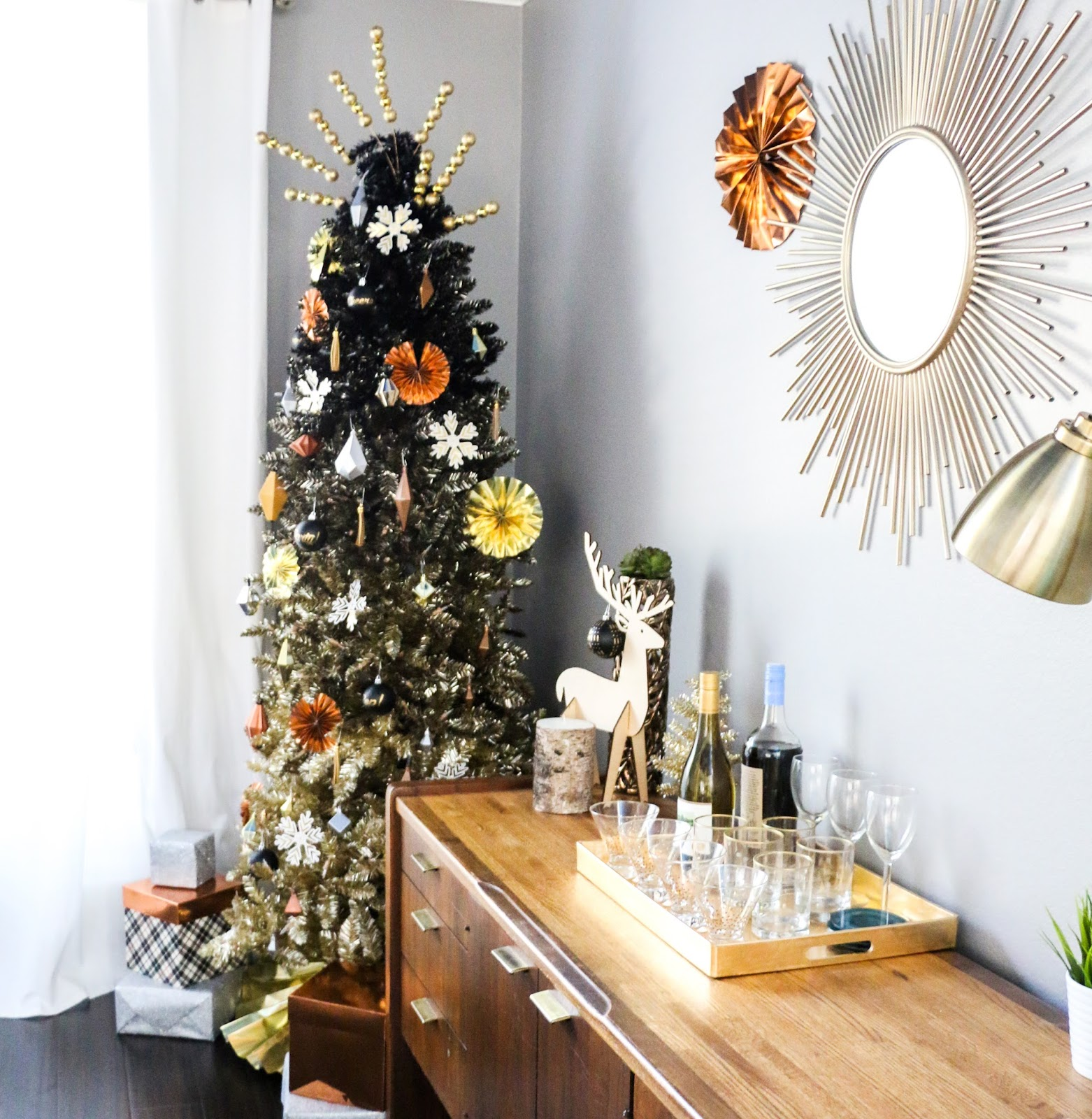 the mix of geometric ornaments and paper fans in a variety of metal colors is definitely not traditional christmas but still exudes a holiday party vibe