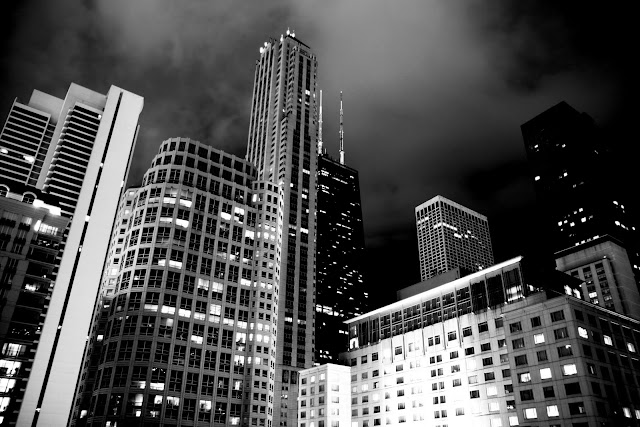 A black and white view Chicago buildings at night from an apartment balcony.
