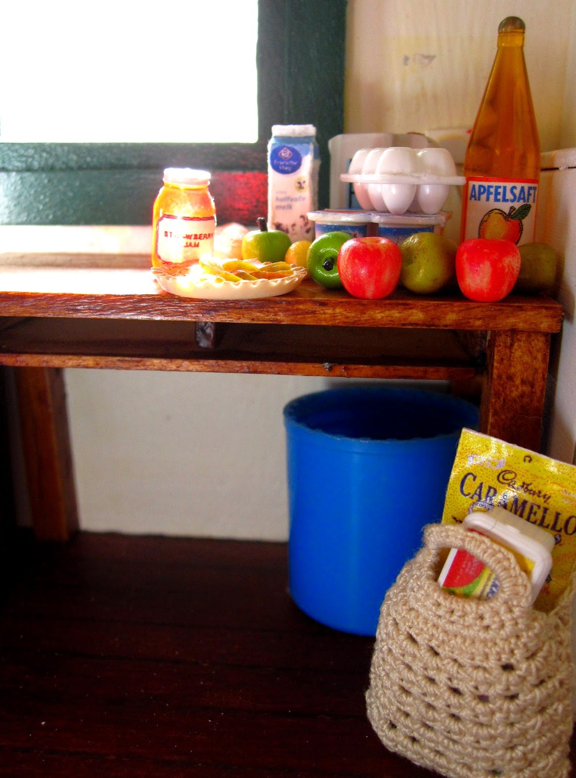 Inside of a miniature holiday house, showing a table with a selection of miniature grocery items, and a bag of groceries is on the floor underneath,