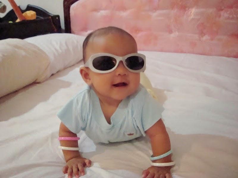 Foto gratis bayi lucu memakai kacamata hitam dan putih di atas tempat tidur