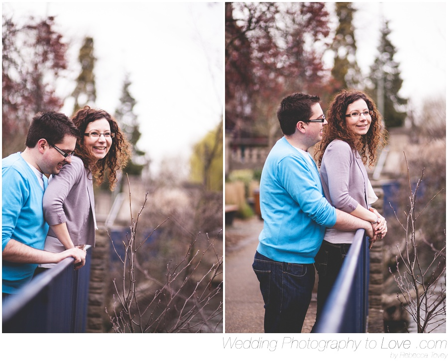 couple standing by a fence smiling