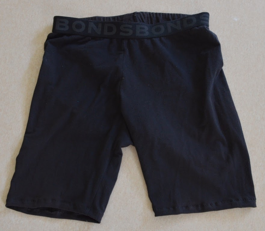 Black, short-mid thigh length bike shorts laid flat.