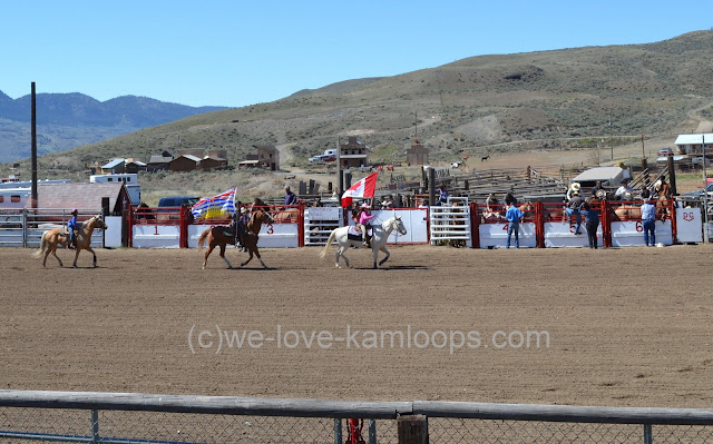 Riders on horseback carry the flags around the ring