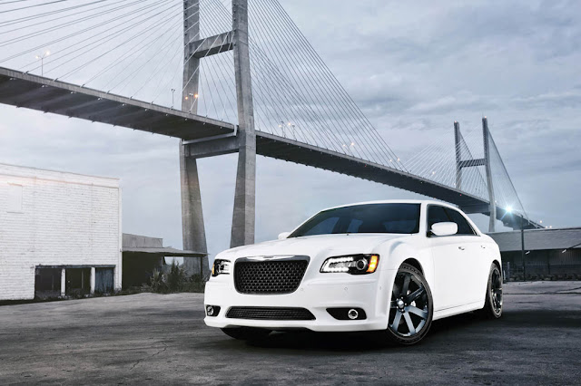 Front 3/4 view of white 2012 Chrysler 300 SRT8 in front of bridge