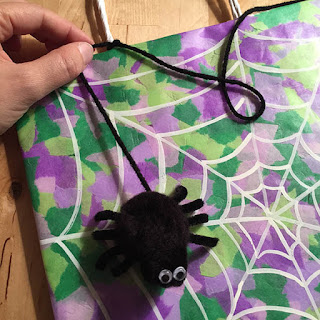 Attaching a cute black pom pom spider with googly eyes to a trick or treat bag