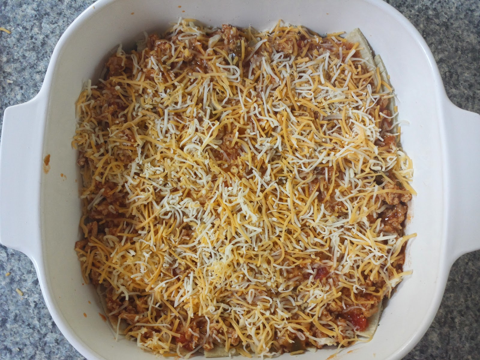 adding cheese to the enchilada bake