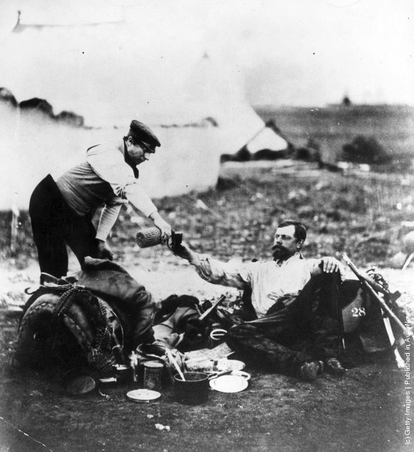 being poured a drink at an army camp in Russia, during the Crimean ...