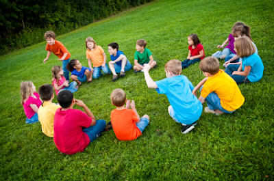 NAMC montessori advantage what is redshirting children playing outdoors in circle