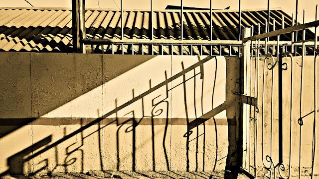 На платформе. Около-железнодорожное. Фотография железная дорога черно-белая сепия ограда тень крыша шифер волна прутья металлические железные острые крашеная облупившаяся краска стена